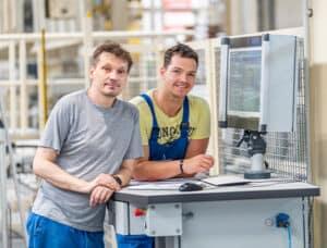 Zwei Mitarbeiter in Produktionshalle an Maschine